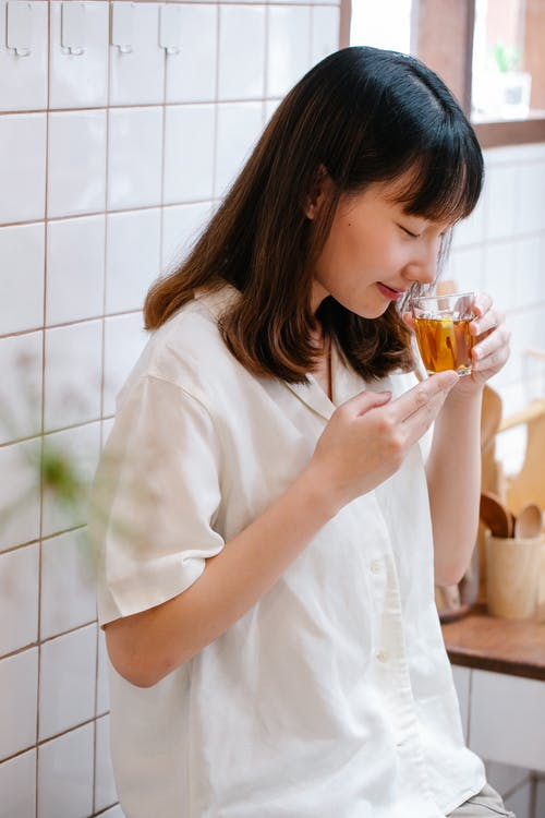 Woman in White Shirt Holding Clear Drinking Glass