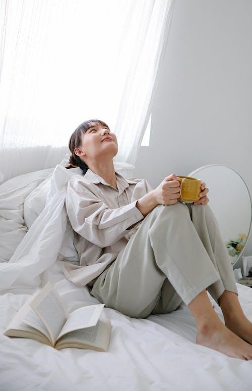 Woman in White Robe Holding Yellow Ceramic Mug