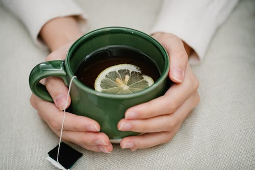 Person Holding Green Ceramic Mug With Brown Liquid