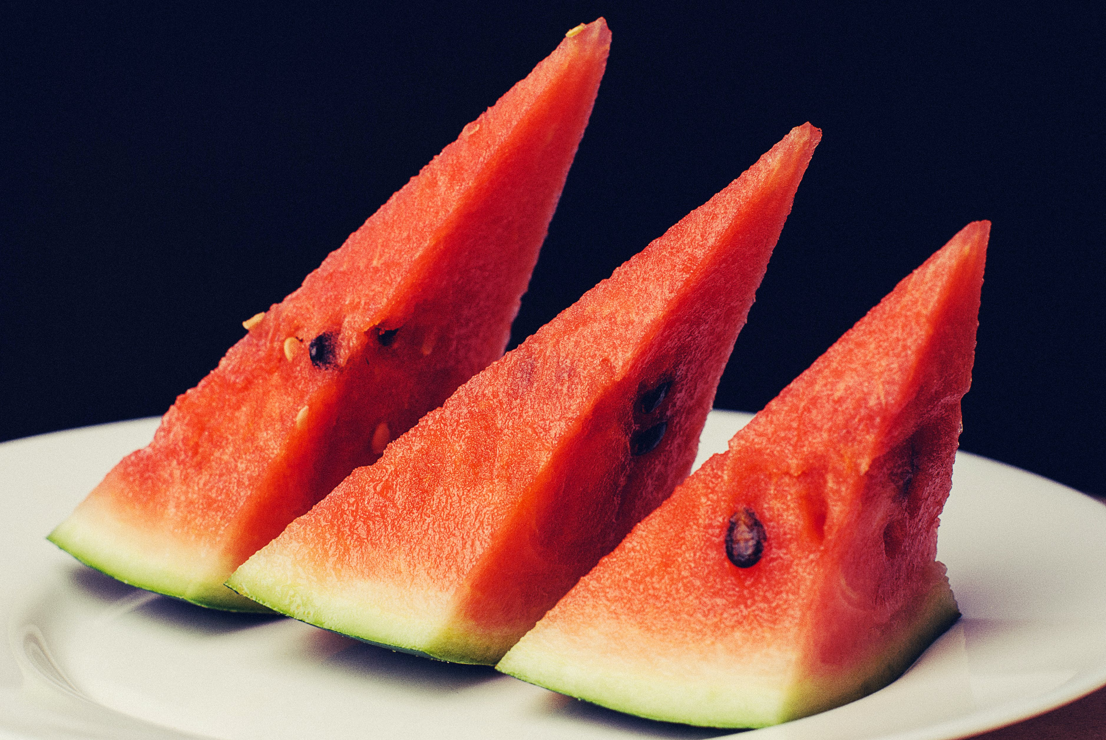 Three Slices of Watermelon on Round White Ceramic Plate