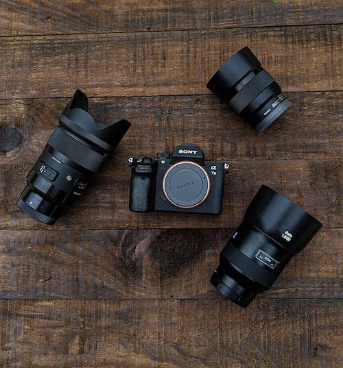 Black Nikon Dslr Camera Lens on Brown Wooden Table
