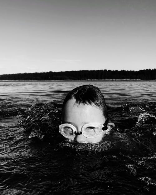 Grayscale Photo of Boy in Water