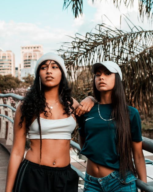 Woman in Blue Shirt and Blue Denim Shorts Standing Beside Woman in White Crop Top and