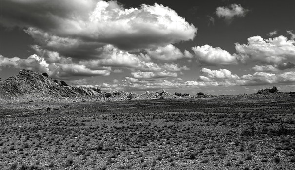 Grey Scale Photography of Open Field and Mountain