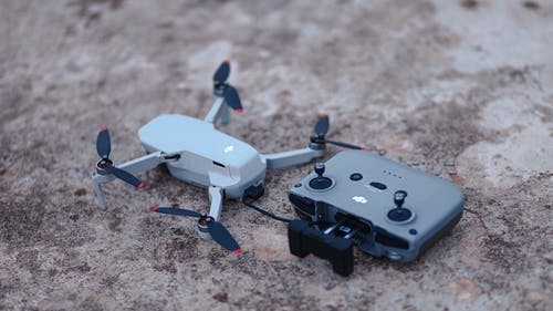 White and Black Drone on Brown and Black Marble Table