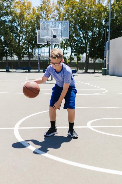 Boy in Blue Shirt and Blue Shirt Playing Basketball