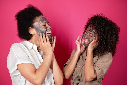 Black women touching cheeks with applied mask in studio