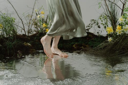 Woman in Gray Dress Standing on Water