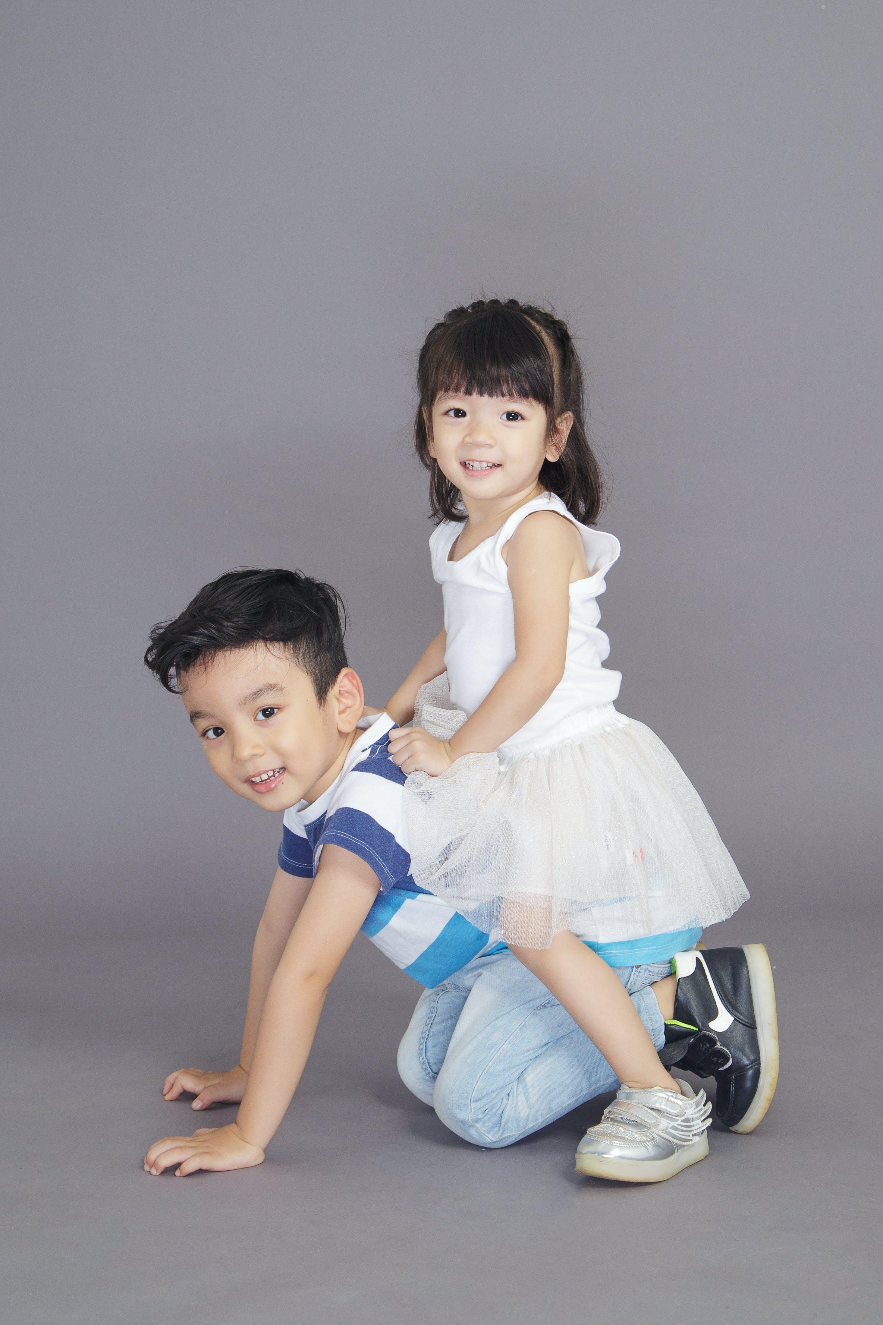 Girl in White Dress Sitting on Crawling Boy's Back