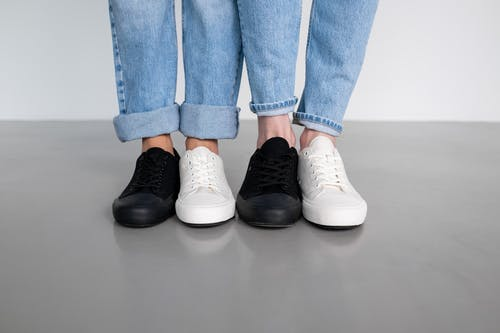 People in Blue Denim Jeans and Black and White Sneakers