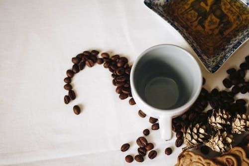 Brown Coffee Beans Near White Ceramic Mug