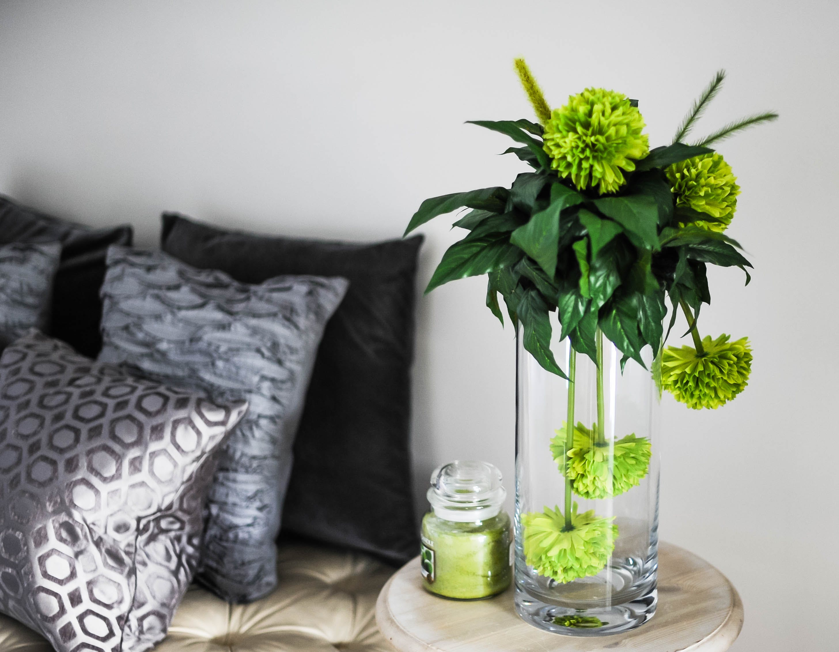 Clear Glass Vase With Green Flowers on Brown Wooden End Table