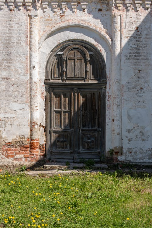 Brown Wooden Arched Door on Concrete Building