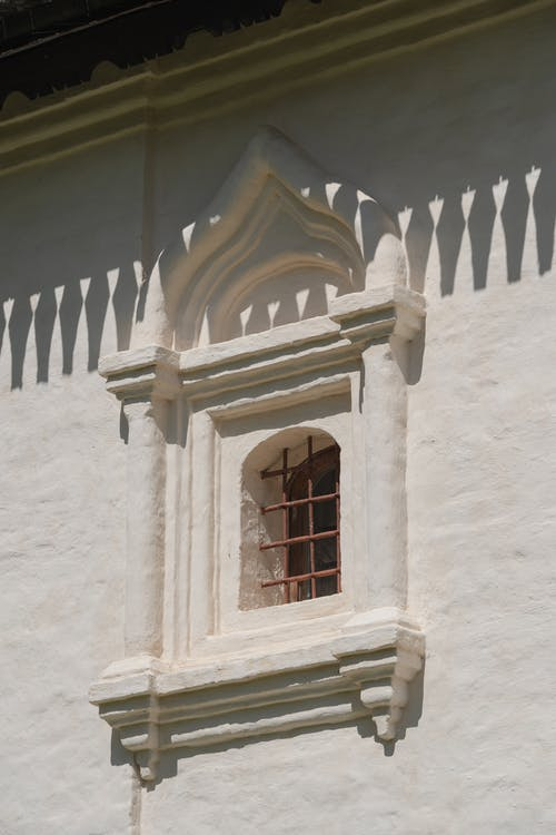 Arched Window With Bars on White Concrete Building