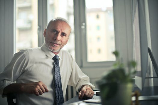 Man Sitting on Chair Beside Table