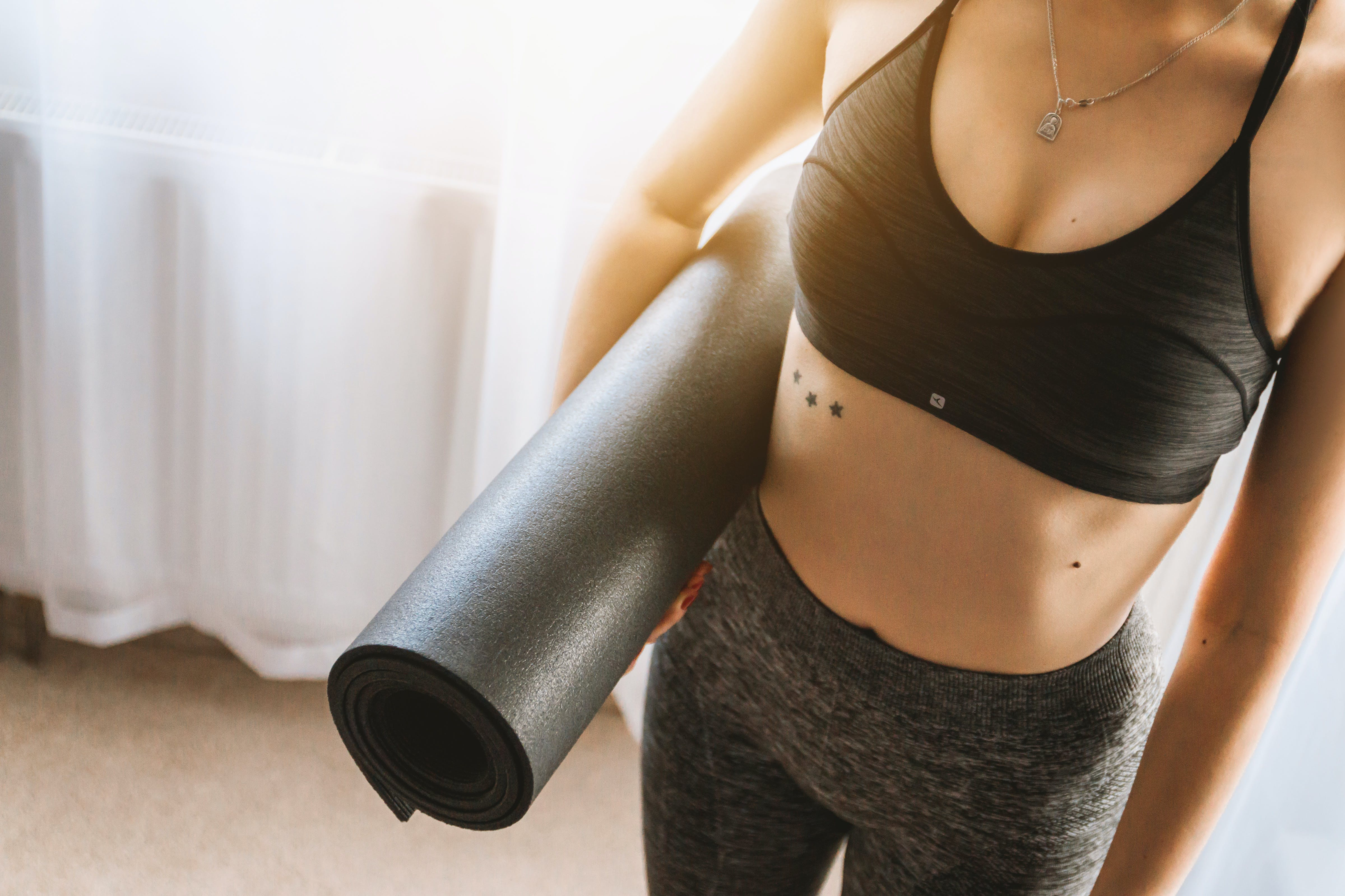 Woman in Black Sports Bra With Grey Leggings Carrying Yoga Mat