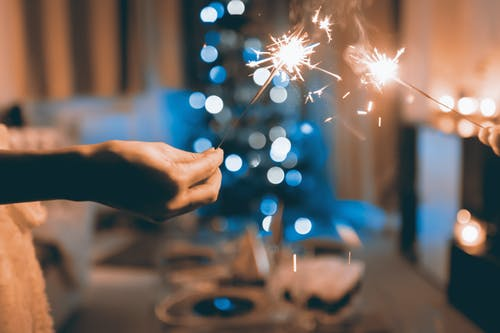 Close Up Photograph of Two Person Holding Sparklers