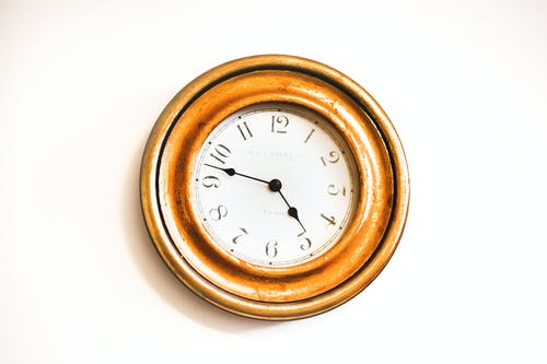 White and Brown Wall Clock Reading at 4:48