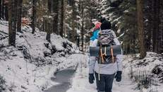 Two People Walking in Woods With Snow