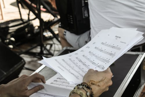 Person Holding White Musical Note Sheets