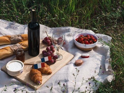 Bread on Brown Wooden Chopping Board Beside Wine Bottle