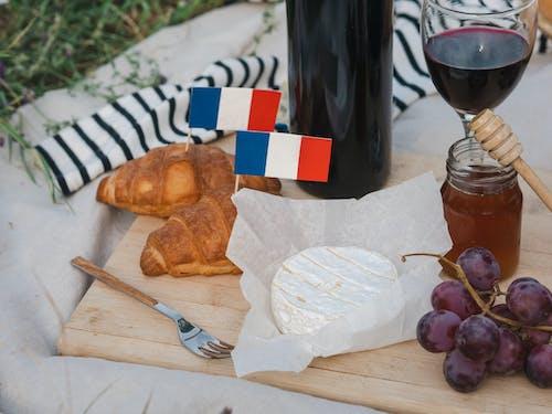 Bread on Brown Wooden Chopping Board Beside Wine Bottle and Wine Glass