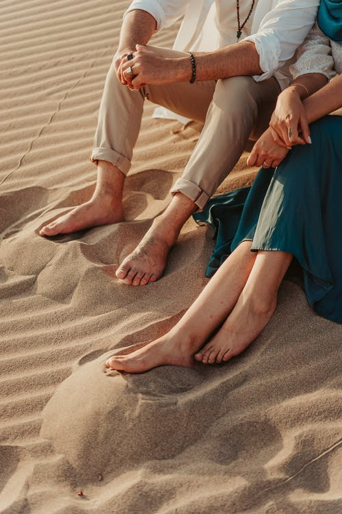 Crop Photo of Two People Sitting on Brown Sand