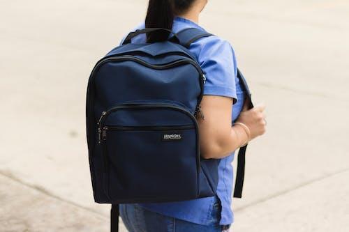 Woman in Blue Denim Jacket Carrying Black Backpack