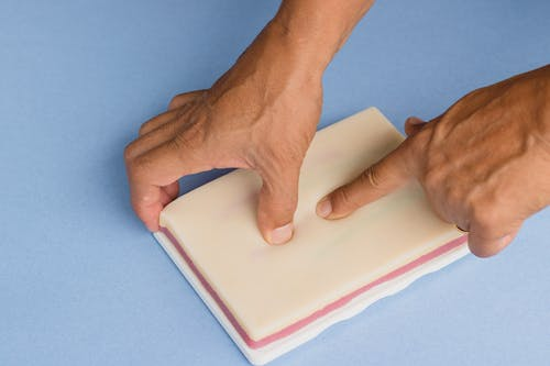 Person Holding White Paper on Purple Textile