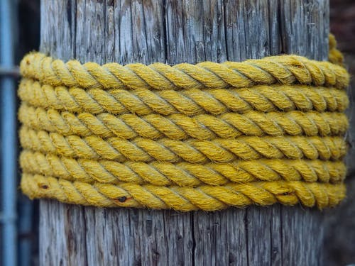 Yellow Rope Wrapped Around A Wooden Post