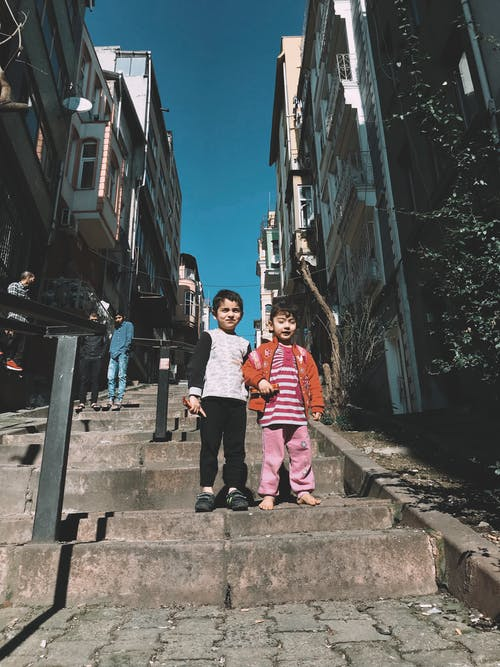 Low-Angle Shot of Two Children Standing on a Concrete Stairs