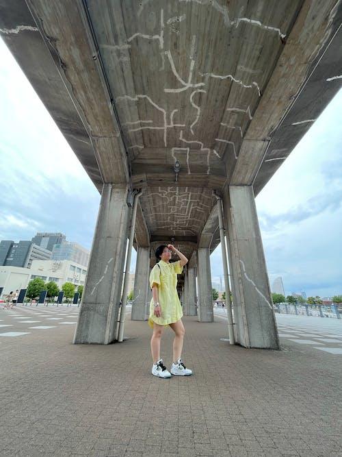 Woman in Yellow Dress Standing on Gray Concrete Bridge