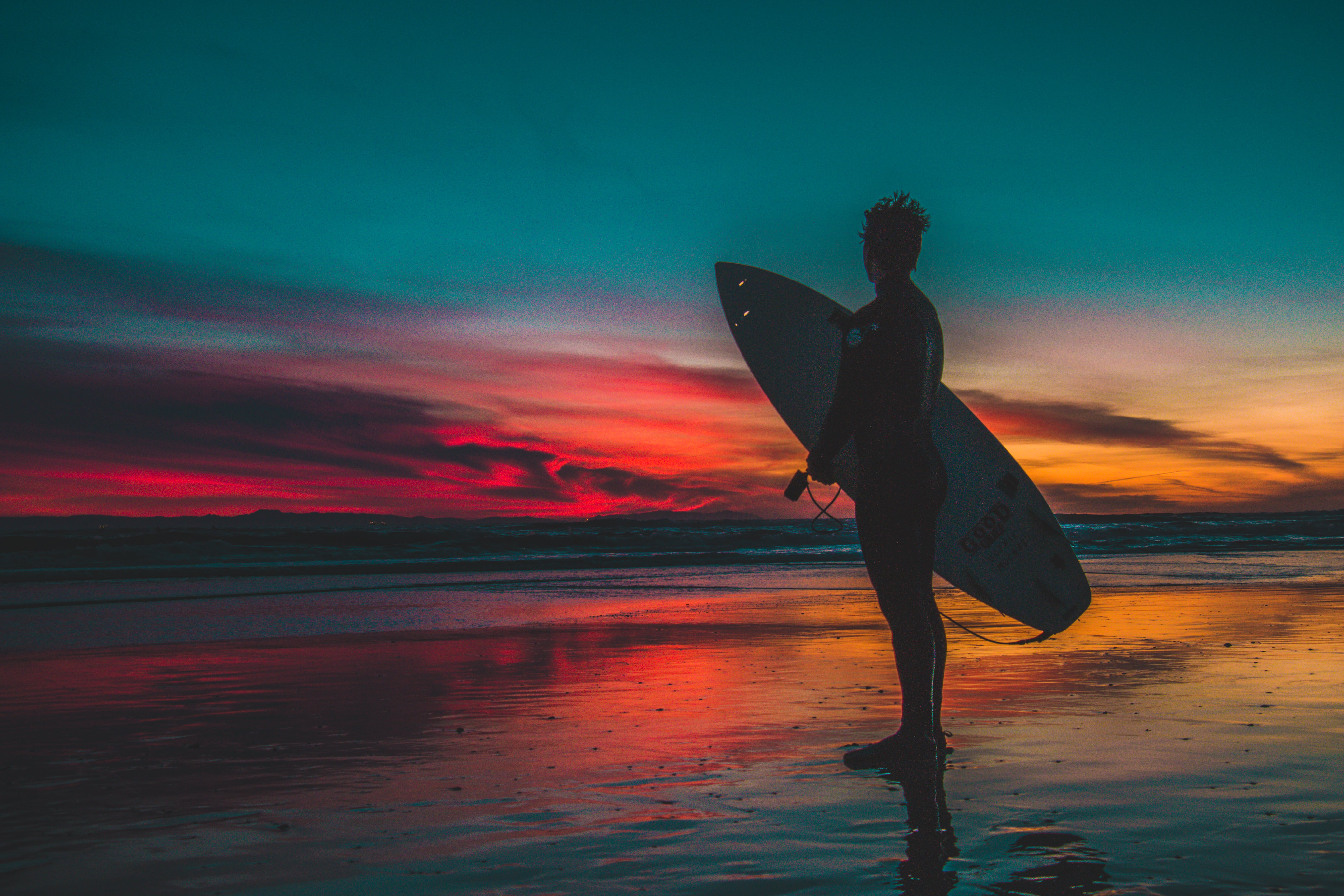 Silhouette of Man in Wet Suit Holding White Surfboard While Standing on Beach during Golden Hour