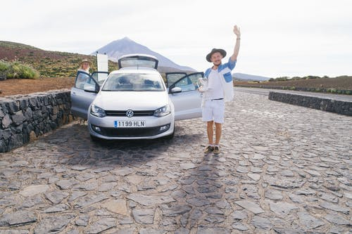 Cheerful male in white clothes standing on cobblestone near car and greeting friend while resting with wife in countryside