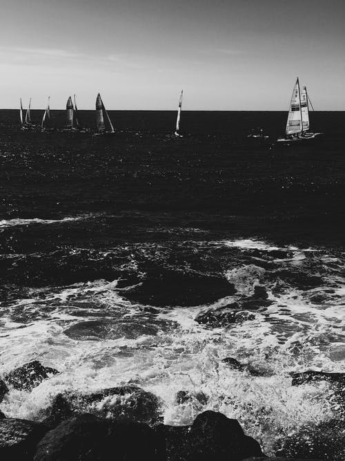 Grayscale Photo of Sail Boat on Sea