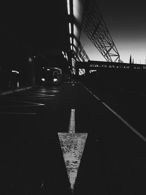 Grayscale Photo of a Road With a Light Post