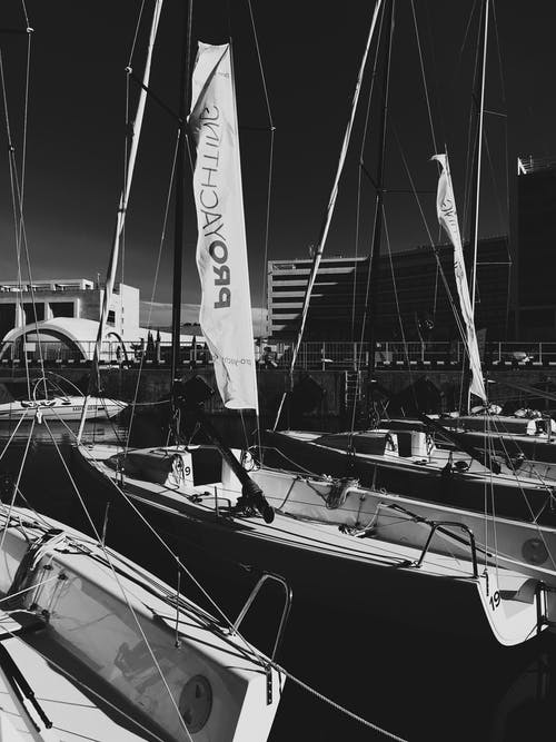 Grayscale Photo of Sail Boat on Body of Water