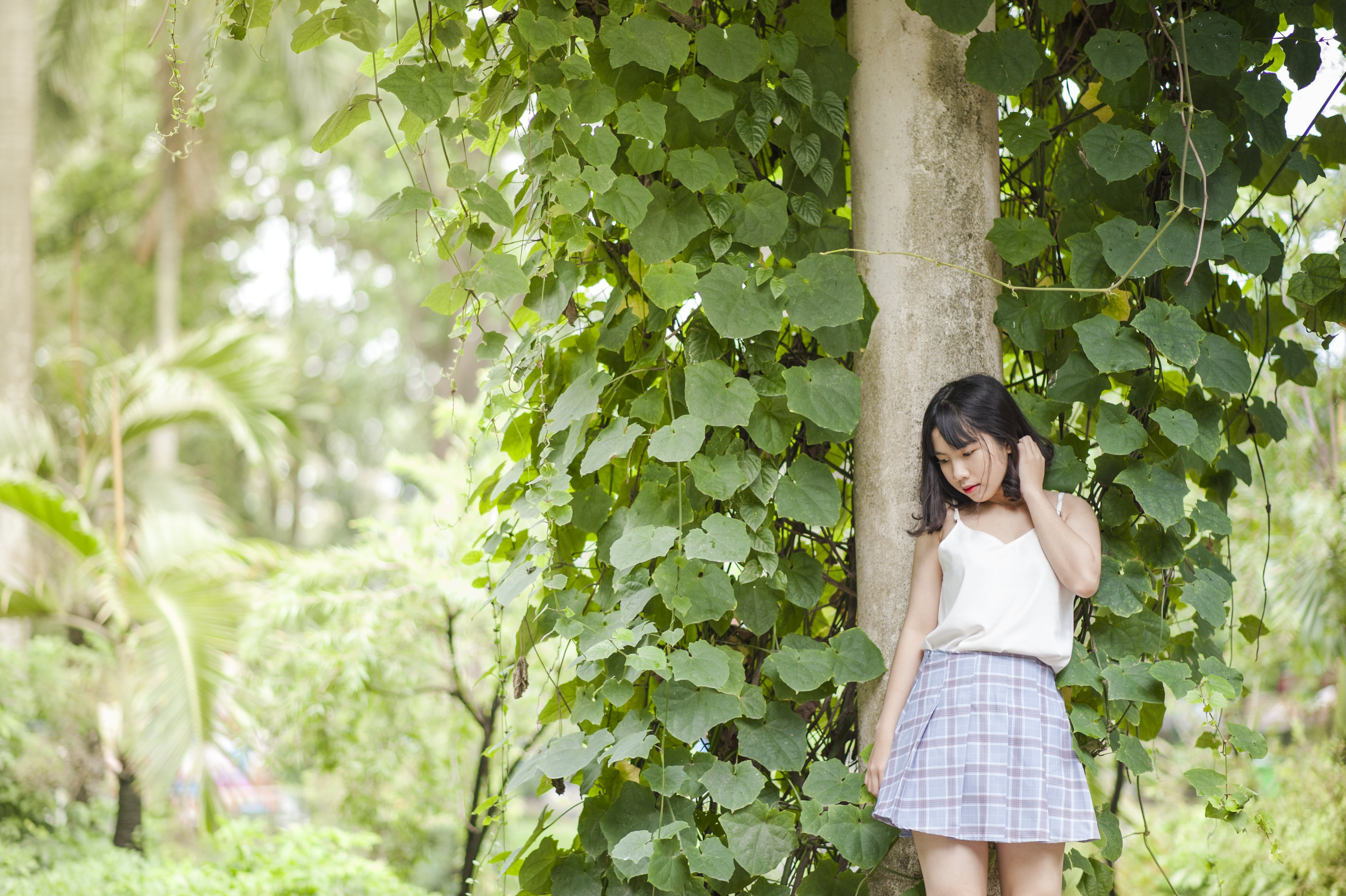 Woman in White Spaghetti Strap Top and Gray Skirt Standing in Front of Tree