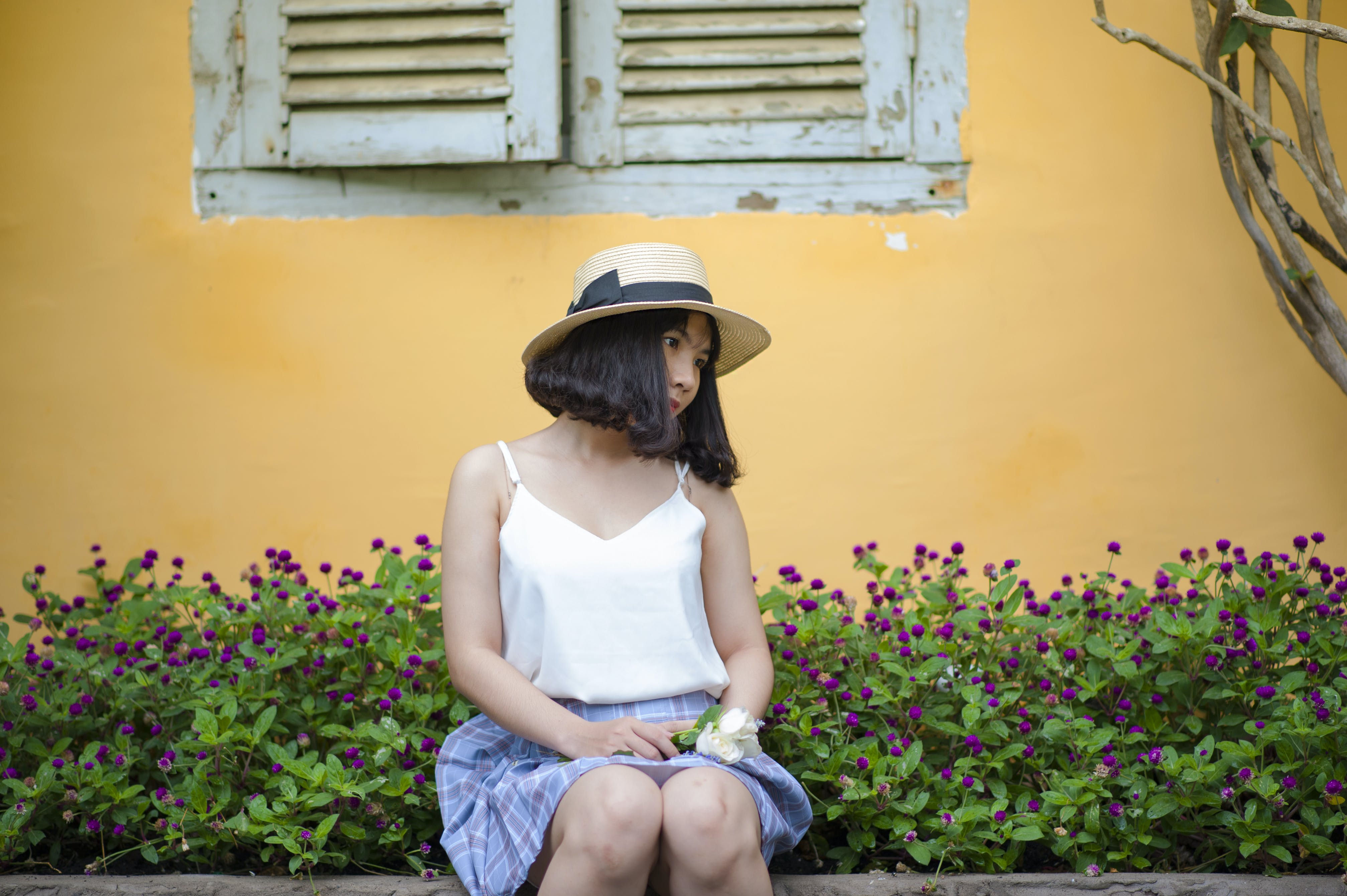 Woman in White Spaghetti Strapped Top With Blue and Purple Plaid Skirt Sitting on Ledge Near Purple Petaled Flower Garden Posing for Photo