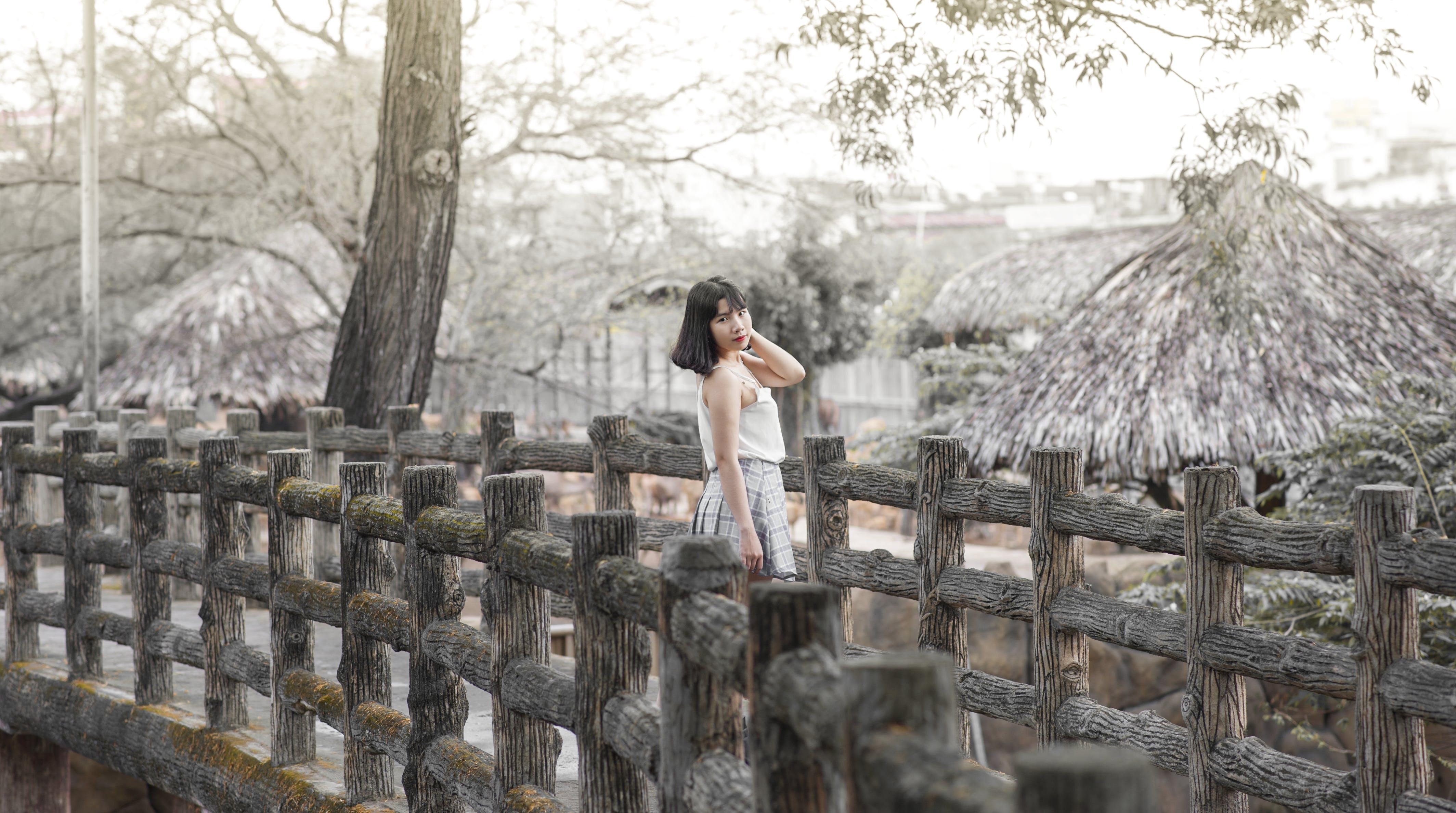 Woman Wearing White Sleeveless Dress Standing on Gray Wooden Dock