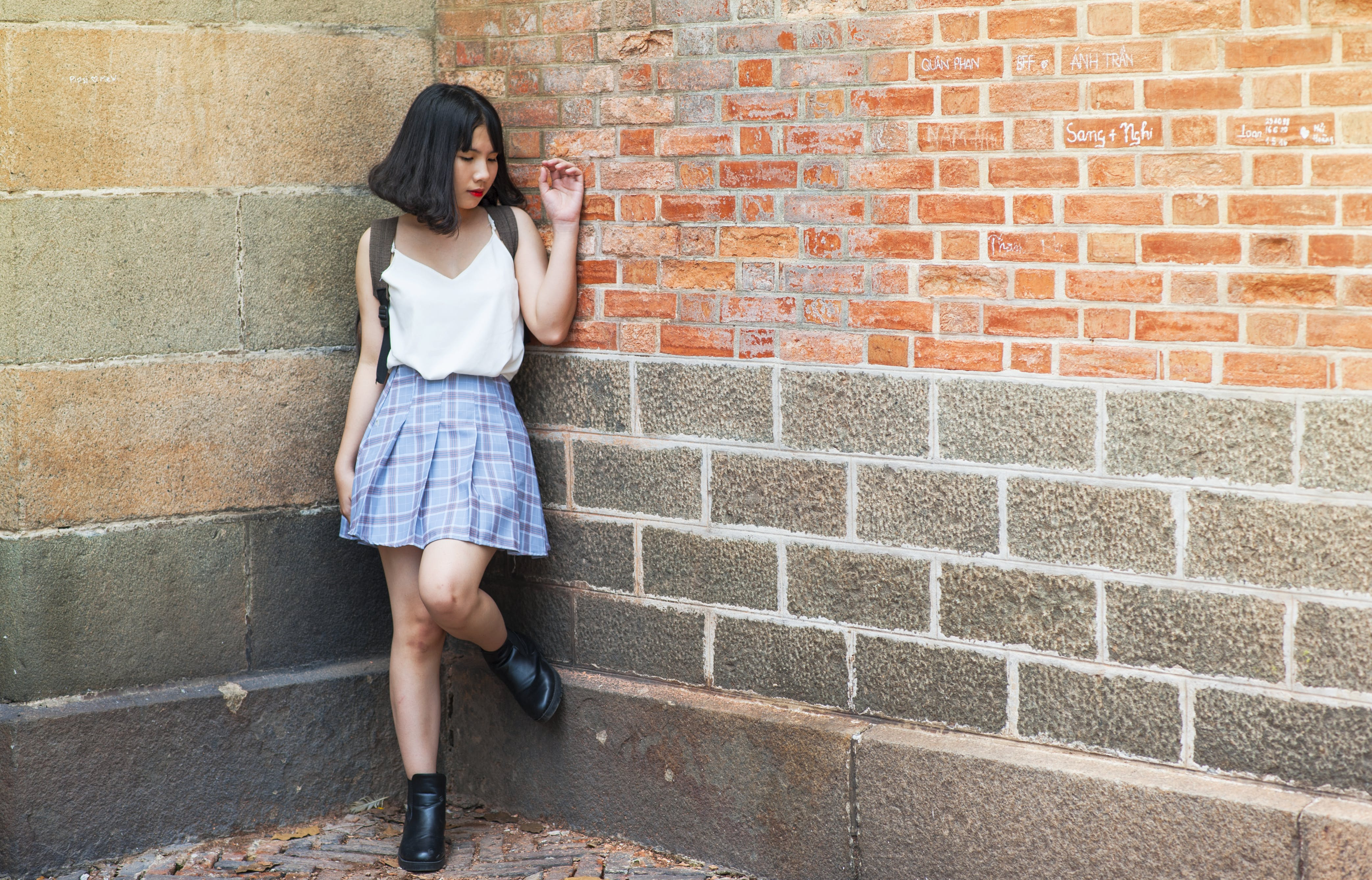 Woman Beside Brick and Cinder Wall