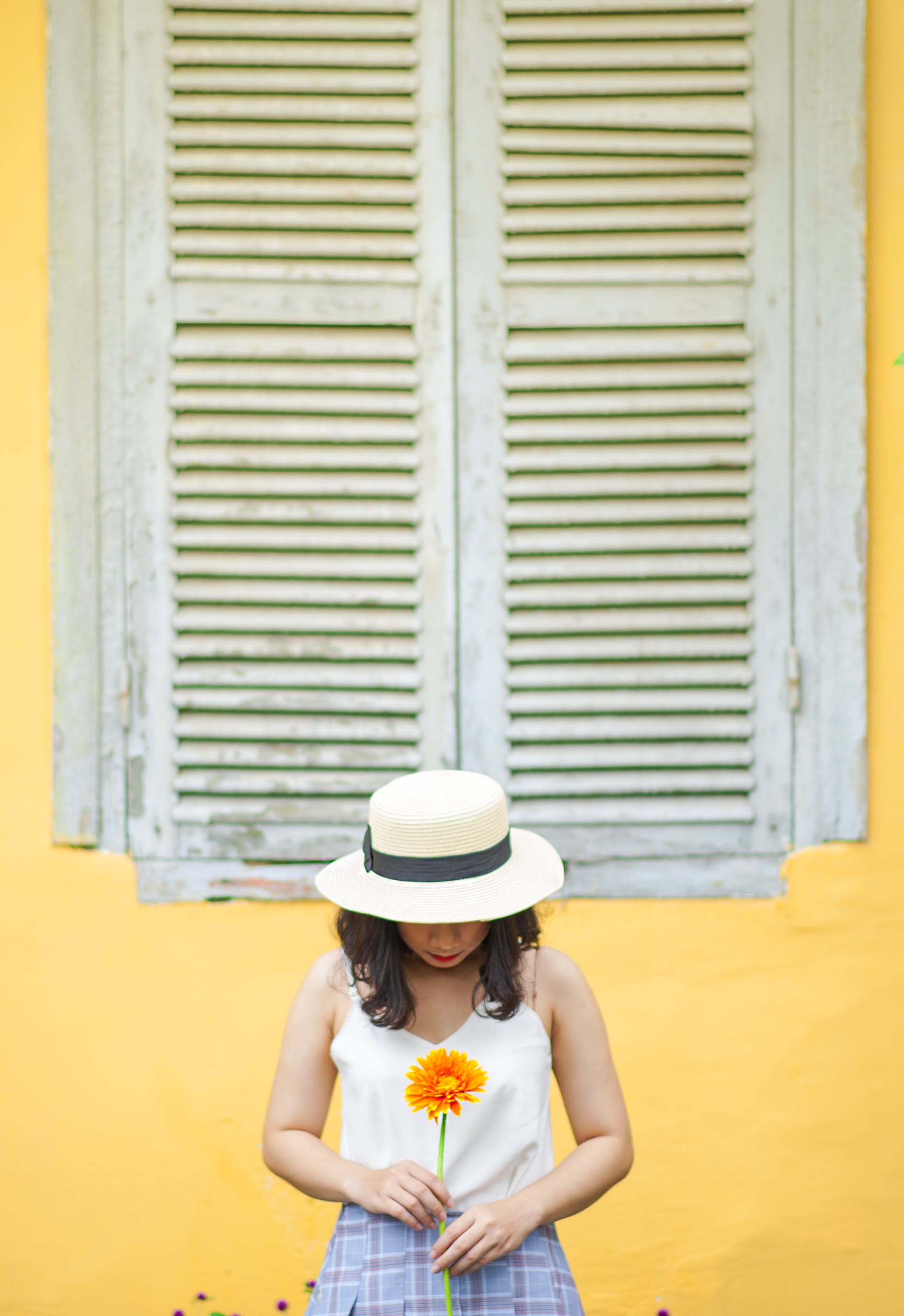 Woman in White Tank Top Holding Sunflower Near Window Outdoors