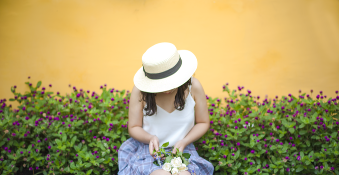 Woman Holding Bunch of White Roses While Sitting Near Flower Fields