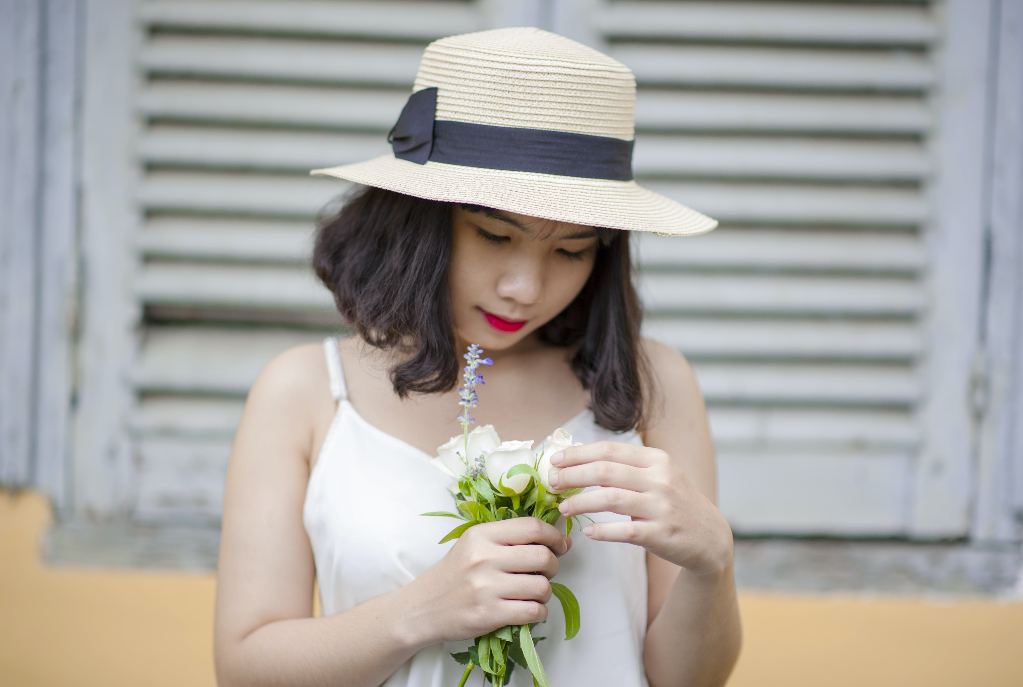 Woman Wearing Beige Sun Hat and White Sleeveless Top Holding White Flowers