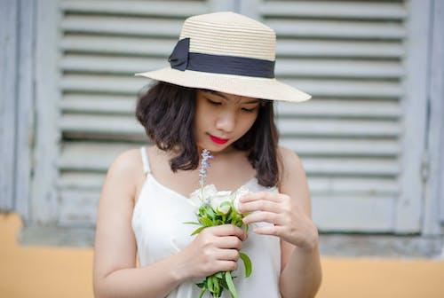 Frau, Die Beige Sonnenhut Und Weißes ärmelloses Oberteil Mit Weißen Blumen Trägt