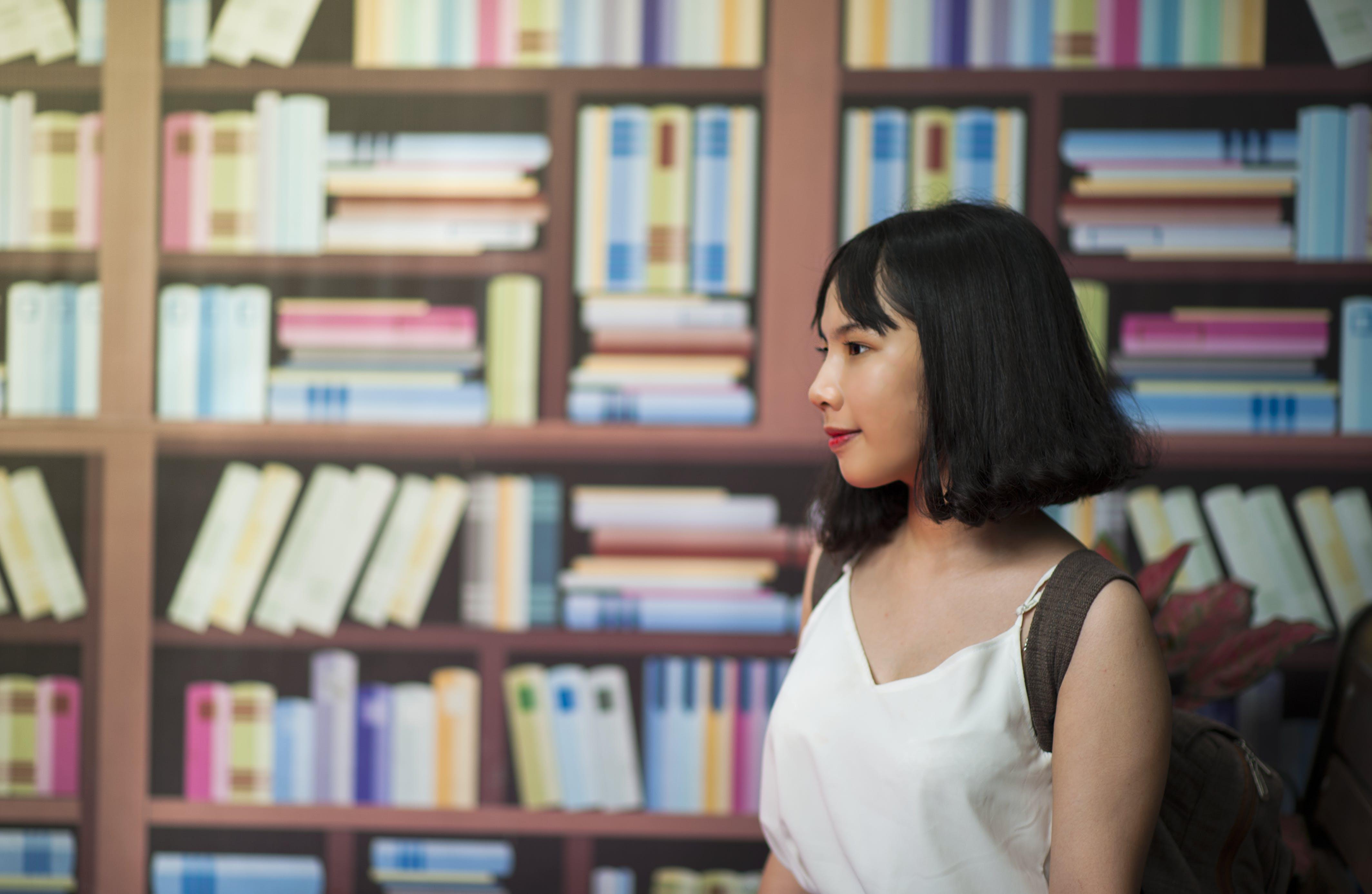 Woman Wearing V-neck Sleeveless Top Near Bookshelf
