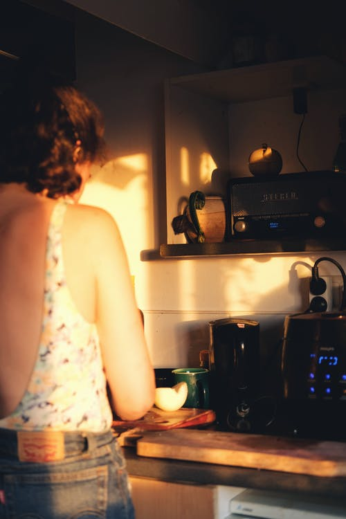 Woman in White Tank Top Standing in Front of Black Microwave Oven