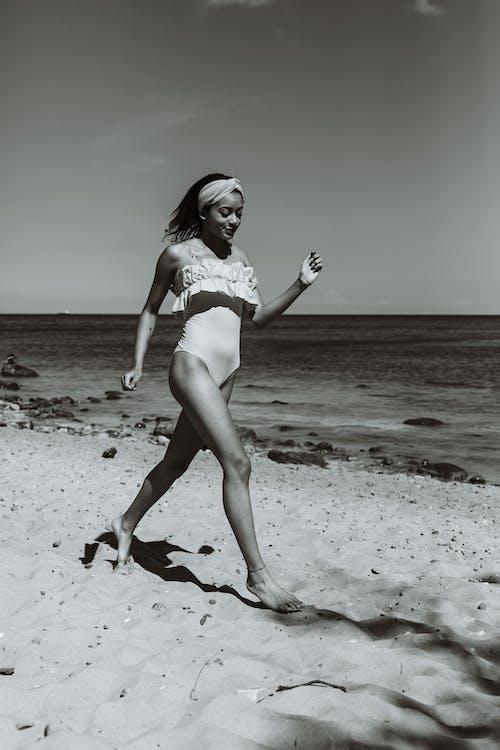Grayscale Photo of Woman in Bikini Standing on Beach