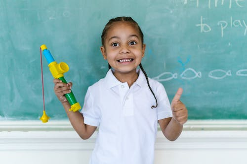Girl in White Polo Shirt Holding Green Plastic Toy