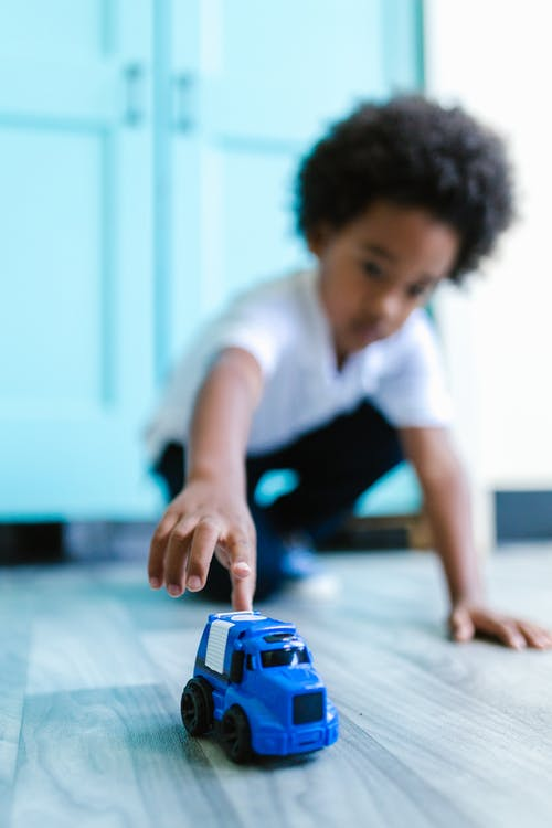 Boy in White T-shirt Holding Blue Toy Car